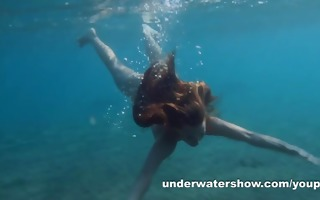 julia is swimming underwater s garb in the sea