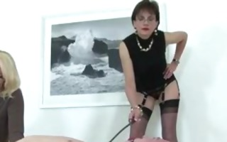 dominatrix instructing apprentice on how to rule